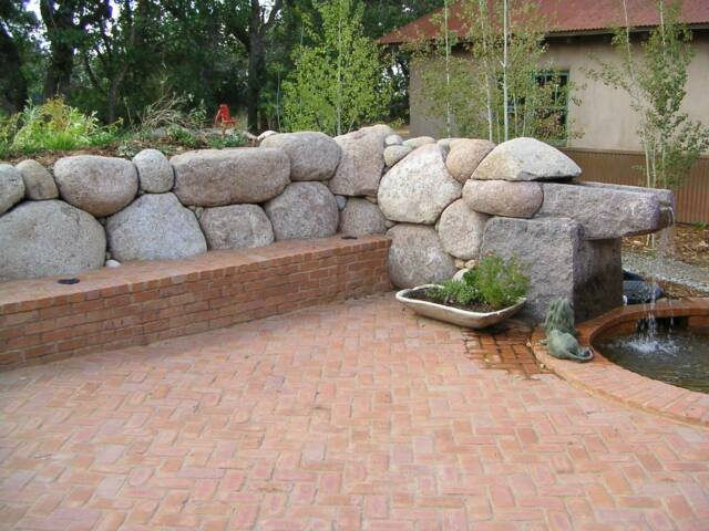 granite boulder retaining wall with quarried granite and brick water feature