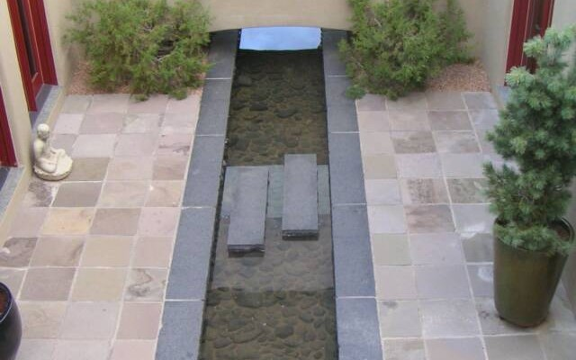 granite water feature lined with river cobble, basalt patio